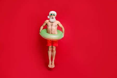 Vista del tamaño del cuerpo de cuerpo entero de agradable atractivo cobarde positivo canoso hombre disfrutando de ocio divirtiéndose junto a la piscina agua de estanque mosca de aire aislada sobre fondo rojo brillante brillo vivo