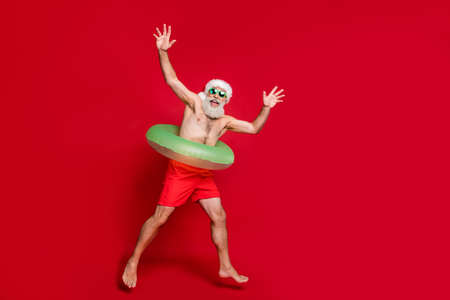 Full length body size view of nice attractive cheerful cheery glad gray-haired man enjoying leisure having fun poolside air fly resort ravel isolated over bright vivid shine red background