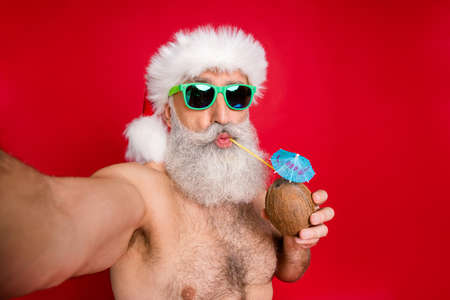 Self-portrait of his he nice attractive funky gray-haired man enjoying leisure free time having fun drinking fresh tasty juice tourist spa resort rest relax isolated over bright vivid shine red background