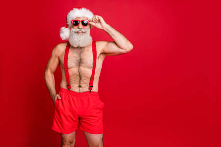 Portrait of his he nice attractive content cheerful cheery funky glad optimistic gray-haired man touching specs enjoying leisure December dream isolated over bright vivid shine red background