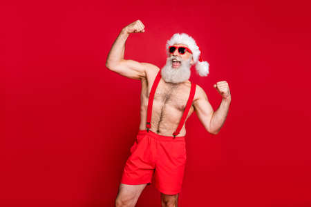 Portrait of his he nice attractive content powerful bearded gray-haired man crossfit trainer instructor bodybuilder showing biceps triceps fit acre isolated over bright vivid shine red background