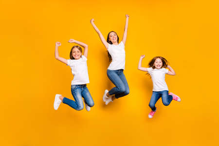 Full size photo of jumping high ladies rejoicing wear casual clothes isolated yellow background