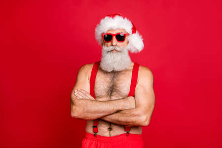Portrait of his he nice attractive content calm gray-haired strong hot muscular macho St Nicholas folded arms festal costume isolated over bright vivid shine red background