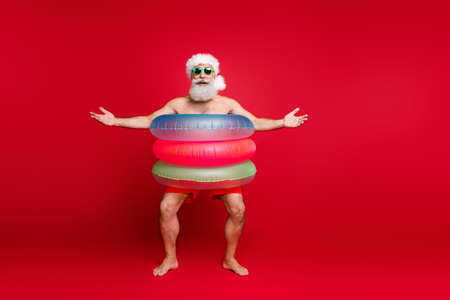 Full length body size view of nice handsome cheerful cheery positive glad carefree bearded gray-haired man wearing air circles pool resort spa hotel isolated on bright vivid shine red background