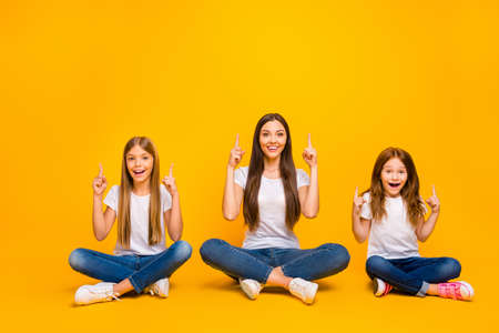Photo of amazing ladies sitting floor with crossed legs indicating empty space wear casual clothes isolated yellow background