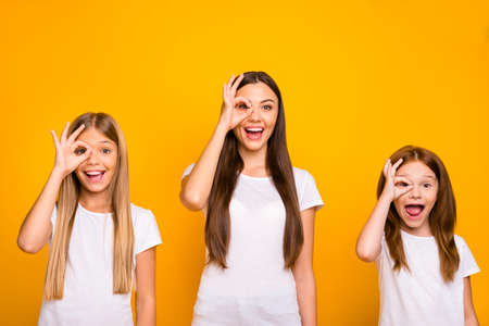 Funny three sister ladies holding hands in okey symbols near eye like specs wear casual outfit isolated yellow background