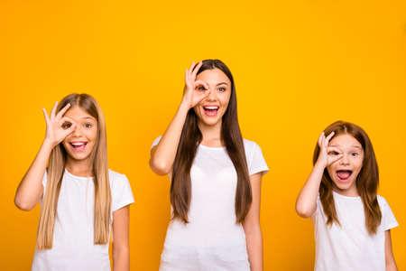 Graciosas tres señoras de la hermana tomados de la mano en símbolos okey cerca del ojo como especificaciones usan ropa casual aislado fondo amarillo Foto de archivo