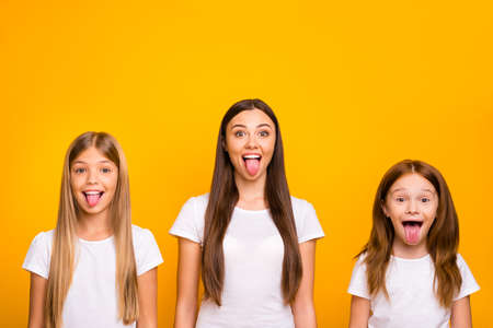 Photo of three different age ladies fooling around together wear casual white t-shirts isolated yellow background Stockfoto