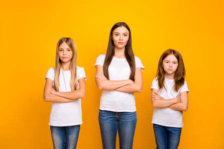 Photo of three sister ladies attentively listening not smiling wear casual white t-shirts isolated yellow background