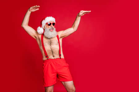 Portrait of his he nice attractive cheerful cheery funky positive playful gray-haired man having fun St Saint Nicholas holly jolly jingle bells isolated over bright vivid shine red background Stockfoto