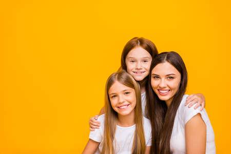 Foto de tres increíbles damas de diferentes edades abrazándose llevar ropa casual aislado fondo amarillo Foto de archivo