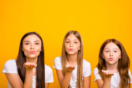 Photo of three coquette sister ladies sending air kisses wear casual white t-shirts isolated yellow background