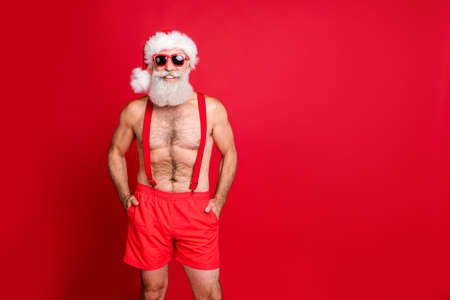 Portrait of his he nice attractive confident bearded muscular fit cheerful funky gray-haired man holding hands in pockets christmastime travel isolated over bright vivid shine red background
