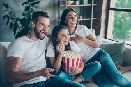 Retrato de agradable atractivo encantador positivo alegre alegre alegre familia vistiendo casual camisetas blancas jeans denim sentado en el sofá divirtiéndose viendo videos divertidos disfrutando de pasar el tiempo libre