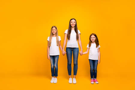 Photo of three sister ladies holding arms glad to be together at weekend wear casual outfit isolated yellow background