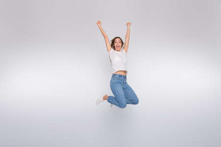 Full length body size photo of jumping happy gorgeous cute attractive girl having won some contests while isolated with white background