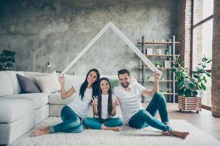 Portrait of nice attractive cheerful family in casual white t-shirts jeans sitting on carpet floor holding in hand roof real estate ownership showing v-sign at industrial loft style interior living-room Banque d'images