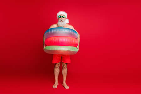Full length body size view of nice handsome cheerful cheery positive comic childish playful bearded gray-haired man wearing air circles isolated on bright vivid shine red background Reklamní fotografie