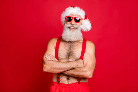 Portrait of his he nice attractive content cheerful cheery funky glad gray-haired muscular macho St Saint Nicholas folded arms wintertime isolated over bright vivid shine red background Stock Photo