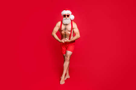Full length body size view of his he nice attractive content powerful cool gray-haired macho trainer instructor bodybuilder gym showing muscles isolated over bright vivid shine red background Stock Photo