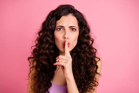 Foto ravvicinata di una ragazza carina e attraente che implora qualcuno di tacere mentre è isolata con sfondo rosa Archivio Fotografico