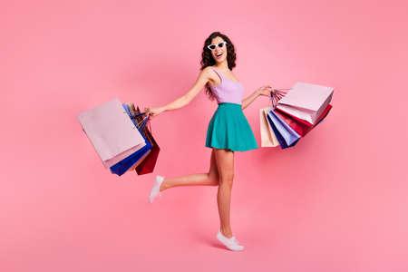 Foto de tamaño de cuerpo entero de alegre, elegante, despreocupada, linda y atractiva mujer hermosa que se regocija con las ventas con falda verde azulado mientras está aislada con fondo pastel