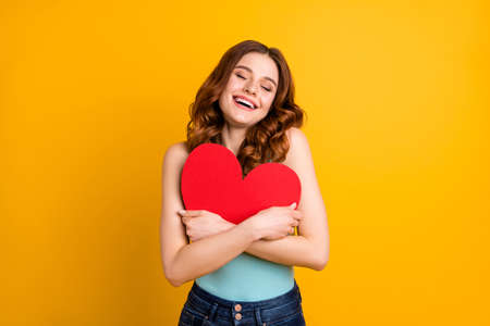 Photo of pretty lady holding big paper heart close to chest wear tank-top and jeans isolated yellow background