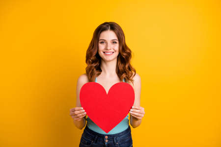Photo of pretty lady holding large paper heart in hands wear tank-top and jeans isolated yellow background