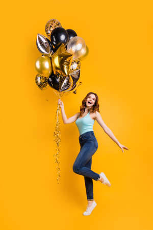 Vertical full body photo of lady having best time with air ballons in hands wear casual outfit isolated yellow background Stock Photo