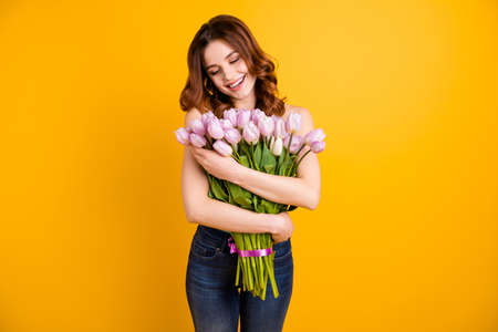 Photo of pretty lady holding close to chest big bunch of pink tulips in arms wear tank-top and jeans isolated yellow background