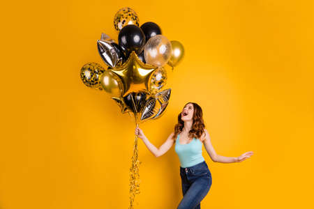 Photo of pretty lady having best weekend with flying air ballons in hands wear tank-top isolated yellow background