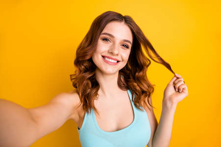 Photo of lady making selfies winding one curl on finger wear tank-top isolated yellow background Stok Fotoğraf