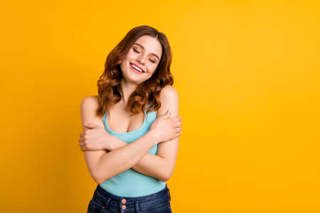 Photo of pretty lady holding hands on shoulders in love with herself wear tank-top isolated yellow background
