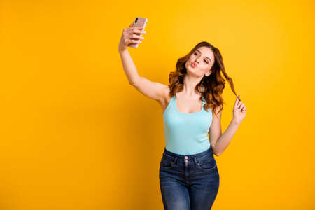 Photo of lady holding telephone making self photos with coquette kisses wear tank-top and jeans isolated yellow background Foto de archivo - 130569593