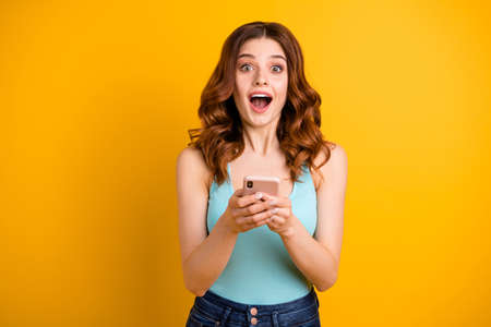 Photo of excited lady with open mouth holding telephone in hands wear blue tank-top isolated yellow background Stock Photo