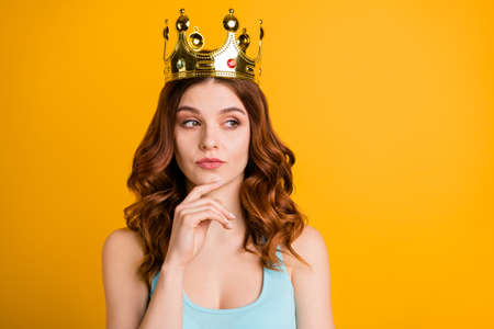 Photo of foxy strict lady not sure about making decision wear tank-top and big golden crown isolated yellow background
