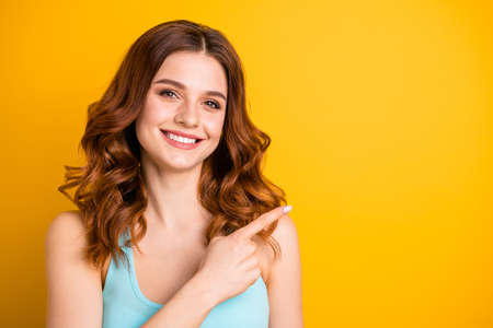 Copyspace close up photo of charming sweet cute nice attractive girlfriend pointing at empty space wearing turquoise tank-top while isolated with yellow vibrant color background Stock Photo