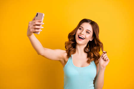 Photo of funny lady holding telephone in hand making self photos wear tank-top isolated yellow background