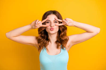 Photo of beautiful ginger foxy trendy cute nice charming lady sending someone a kiss flirty wearing teal tank-top while isolated over yellow vivid color background