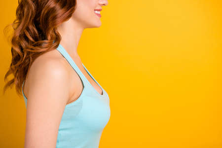 Cropped photo of cheerful nice girlfriend focused on her chest and wearing turquoise tank-top while isolated over yellow vibrant color background