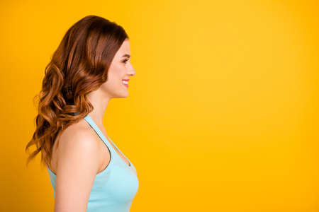 Copyspace photo of charming cute cheerful nice gorgeous fascinating girlfriend looking at something pleasing wearing turquoise tank-top isolated with yellow bright color background