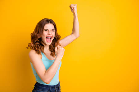 Turned photo of beautiful cheerful trendy pretty rejoicing excited girlfriend wearing turquoise tank-top jeans denim while isolated over yellow vibrant color background Stock Photo - 130569840