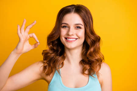 Close up photo of charming pretty sweet nice girlfriend wearing teal singlet showing you ok sign while isolated over bright yellow color background