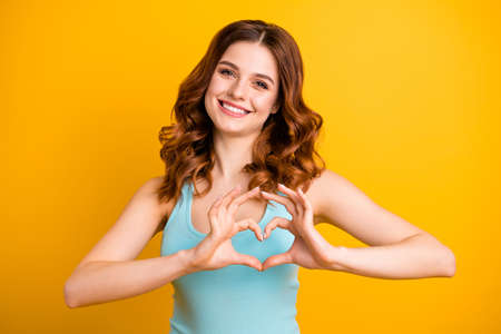 Photo of cute charming pretty attractive good girlfriend feminine and girlish wearing turquoise tank-top smiling toothily showing you heart while isolated with vivid color yellow background