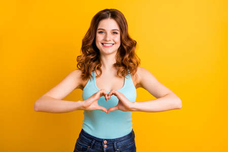 Photo of fascinating attractive curly wavy peaceful thankful trendy student lady showing you heart made with fingers wearing teal singlet jeans denim while isolated with bright color yellow background