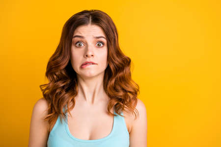Photo of shocked girlfriend biting her lips because of being worried with something she feels guilty with while wearing teal tank-top isolated with vibrant yellow color background Stock Photo