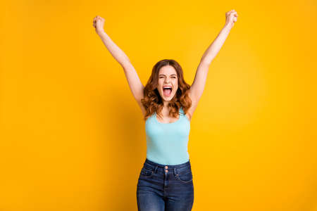 Photo of curly wavy crazy beautiful attractive rejoicing overjoyed girlfriend wearing turquoise tank-top jeans denim grimacing while isolated with yellow vivid color background Фото со стока