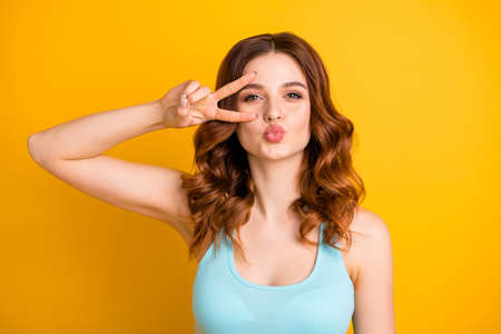 Photo of cheerful trendy cute nice charming fascinating gorgeous girlfriend kissing someone while showing v-sign wearing teal tank-top being isolated over yellow vivid color background