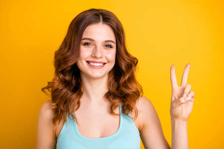 Photo of charming beautiful cute attractive nice girlfriend wearing singlet teal showing you v-sign while isolated with yellow background