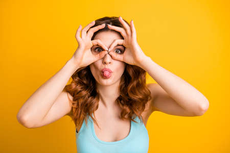 Photo of cute charming beautiful attractive pretty girlfriend wearing teal singlet fooling with her hands making glasses while isolated with yellow vibrant color background